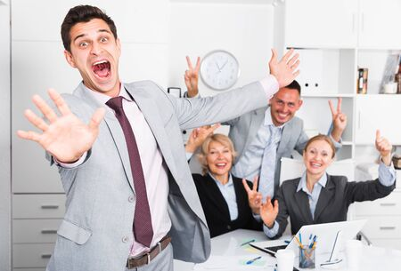 Excited businessman with happy team behind emotionally gesturing and celebrating victory at office