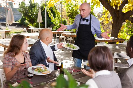 Restaurant guests complain about the food to the waiter Foto de archivo