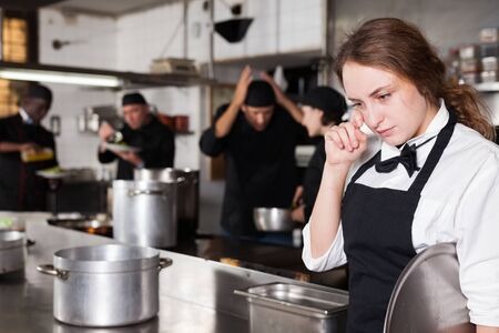 Tired and upset waitress in kitchen of restaurant 写真素材
