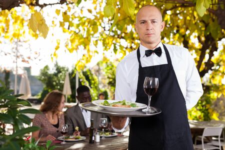 Adult waiter serves customers in a open-air restaurant 写真素材