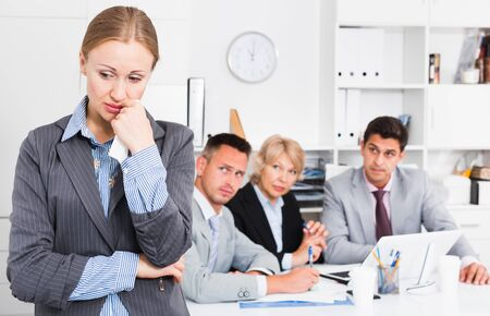 Unhappy and crying woman standing at office on background with coworkers Archivio Fotografico
