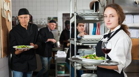 Professional waitress holding serving tray at restaurant kitchen