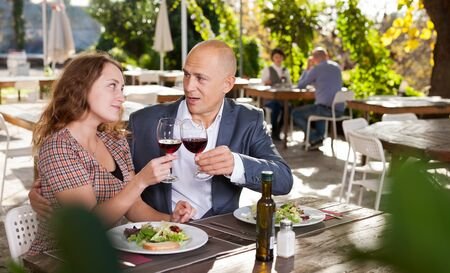 Couple in love drinking red wine at open-air restaurant Stock fotó