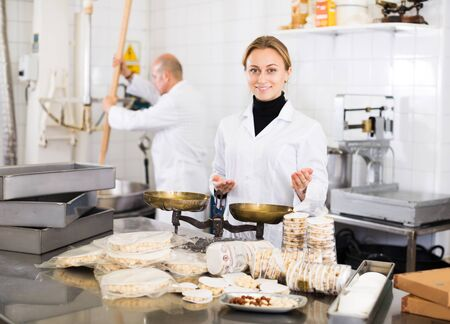 Young woman and adult man workers kipping turron in food manufacture