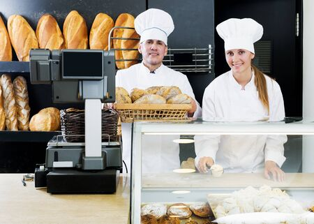 Mature male and happy female staff offering fresh baguettes and buns in bakery