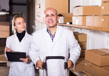 Young female and happy adult male transporting cart cardboard cases in storage