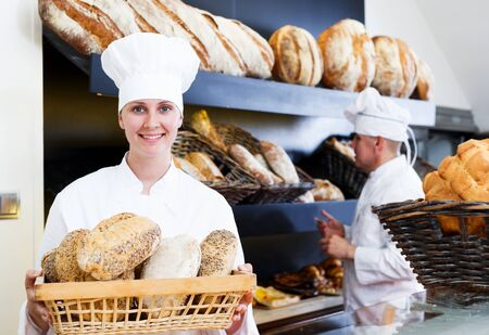 Male and cheerful female staff offering fresh baguettes and buns in bakery 版權商用圖片
