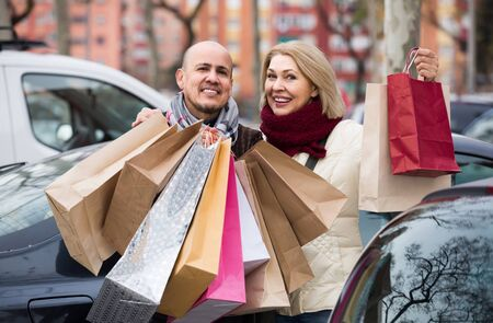 Happy russian elderly couple carrying purchases and smiling outdoors Stock fotó