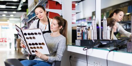 Young pleasant cheerful female hairdresser with woman client looking samples of hair dye in beauty salon 写真素材