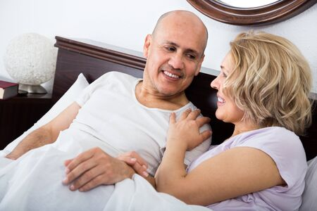 Positive mature adults lying in family bed and smiling