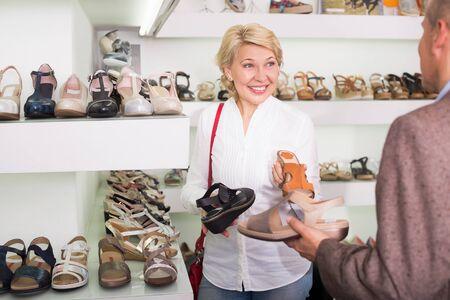 Vrouw en man maken keuze tussen grote variatie aan modeschoenen in de winkel