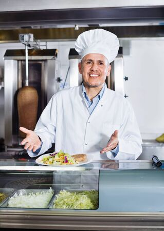 Smiling  pleasant mature man cook serving fresh kebab dish on plate in fast food restaurant