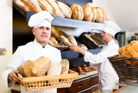 Happy male and female staff offering fresh baguettes and buns in bakery