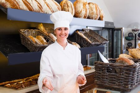 Woman baker is offering fresh baguettes and buns in bakery.