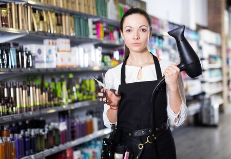 Female hairdresser in apron holding blow dryer and hair cutters in beauty studio
