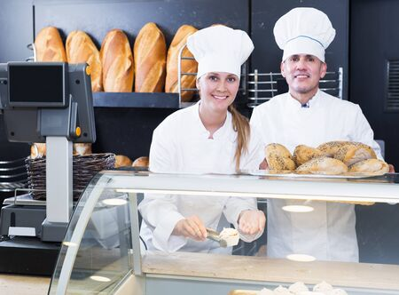 Portrait of positive male and female bakery employees offering delicious bread in bakery 版權商用圖片