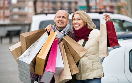 Portrait of smiling positive pleasant mature couple standing near car with shopping bags Stok Fotoğraf