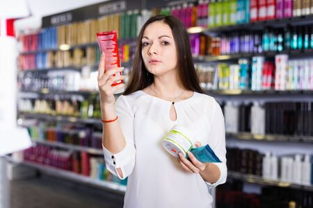 Serious glad pleasant friendly young female choosing hair care products at cosmetics showroom