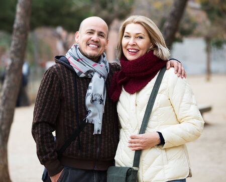 Urban portrait of mature spouses relaxing during walk