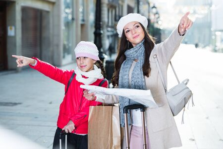 adult female and daughter in the city center in scarf with map