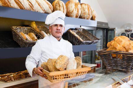Middle aged baker is showing tasty bread in bakery.