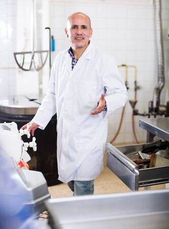 Adult male standing in production workshop in white overalls Stock fotó