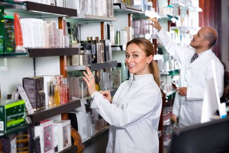 Two efficient female and male pharmacists in white coats working the pharmaceutical store