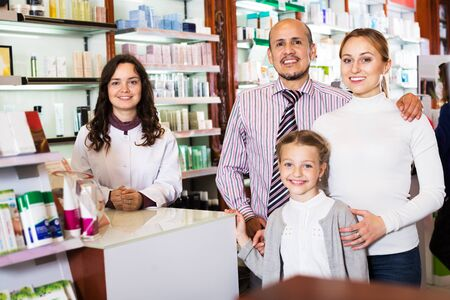 Smiling parents with a small girl standing next to cashier and consulting a pharmacist in drugstore. Focus on man Stok Fotoğraf