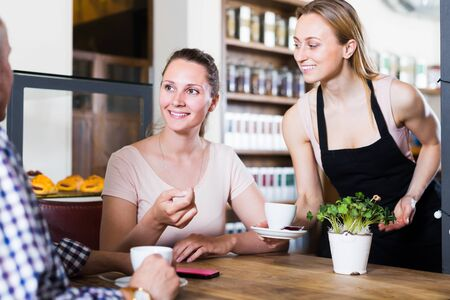 cheerful waiter girl brought cup of coffee for couple of different aged people in a cafe
