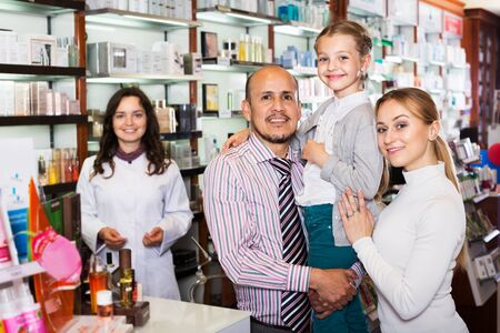 Portrait of happy young parents with a small girl standing next to cashier in pharmacy