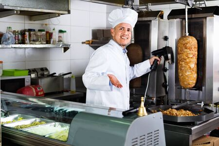 Smiling positive mature man cook cutting kebab meat on kitchen in fast food cafe