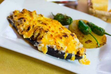 Eggplant  stuffed with meat and baked with bechamel sauce and cheese, served with small pepper