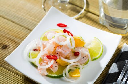 Savory seafood ceviche with shrimps, lime, tangerine, onion rings and sliced red hot pepper
