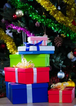 Multicolor New Year gifts against backdrop of dressed Christmas tree