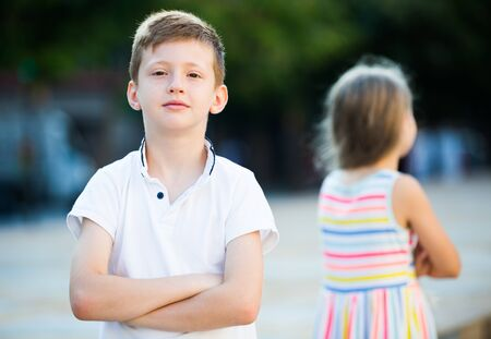 Portrait of angry boy sitting back to friend outdoors in park 版權商用圖片 - 129495740