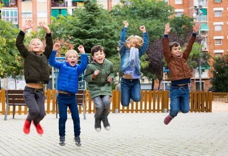 Group of laughing happy children jumping together on playground 写真素材