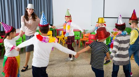Happy kids and female teacher in funny hats and festive accessories dancing together in schoolroom Imagens