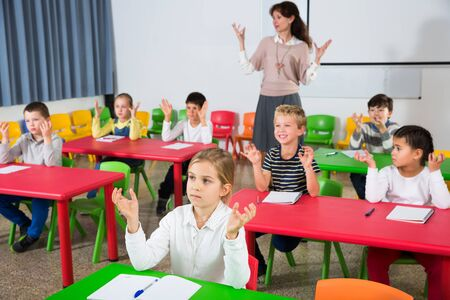 Portrait of children stretching with friendly female teacher during physical activity break in school 写真素材