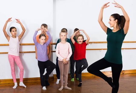 Group of smiling american children practicing at the ballet barre
