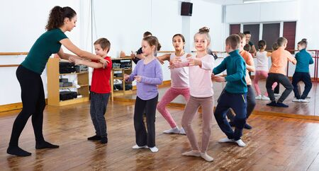 Young smiling efficient ballet dancers exercising in ballroom
