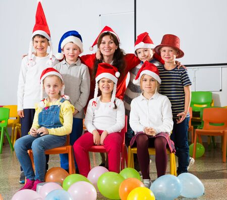 Group of cheerful pupils with female teacher wearing Santa hats posing together in schoolroom Stockfoto