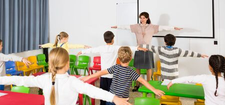 Young friendly female teacher conducting little warm-up with pupils during break in lesson in elementary school