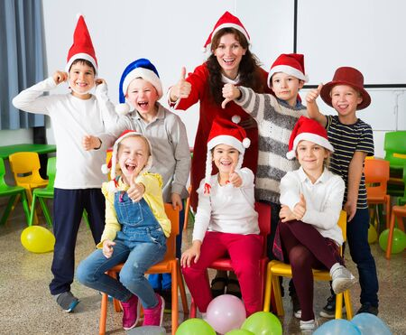 Cheerful group of pupils with female teacher wearing Santa hats posing together in schoolroom, giving thumbs up Stockfoto