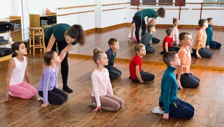 Glad cheerful positive  children dancing contemp in studio smiling and having fun