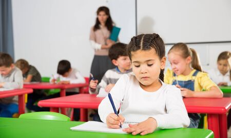Cute intelligent preteen girl studying in classroom on background with classmates and teacher