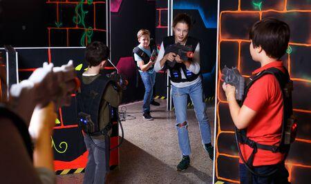 Modern teenage girl and boys with laser guns playing laser tag on dark room Фото со стока