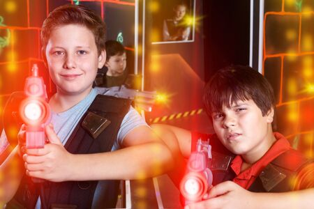 Portrait of two teen boys standing with laser guns ready for lasertag game indoors