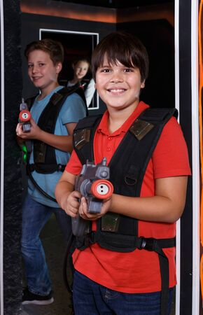 Portrait of two active teen boys standing with laser guns ready for lasertag game indoors