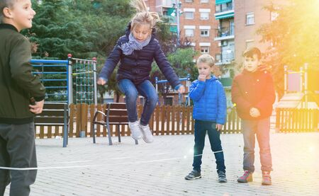 Happy kids skipping on chinese jump rope on playground in autumn day