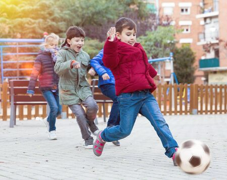 Happy preteen children playing with ball outdoors, running together in yard